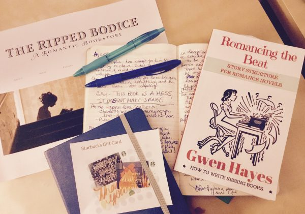Photo of giveaway prizes: notebook, pens, Starbucks and The Ripped Bodice gift cards, Romancing the Beat book